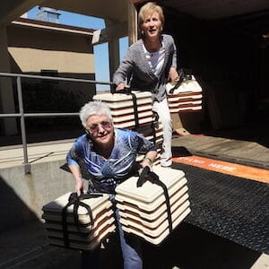 Two women delivering meals to elderly people